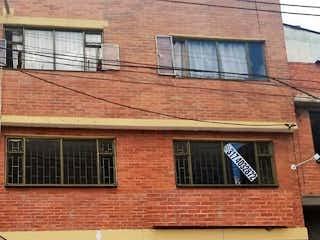 Un edificio de ladrillo con una puerta roja y una ventana en Casa En Venta En Bogota Gaitan