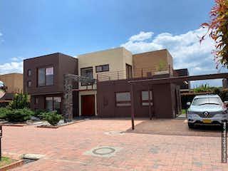 Un edificio de ladrillo con un coche estacionado en frente en ¡Super Oportunidad! Hermosa Casa en Venta, Cajica Cundinamarca