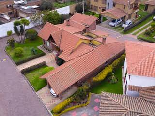 Un banco de madera sentado junto a un edificio en Casa en venta en Casco Urbano Mosquera 526m² con Jardín...