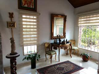 Una sala de estar llena de muebles y una lámpara de araña en Casa en venta Chia, Conjunto Cerrado