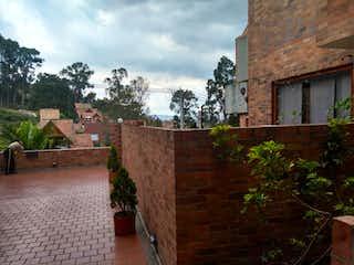 Un gran edificio de ladrillo con un banco en frente de él en Casa En Venta En Bogota Bosque De Pinos-Usaquén