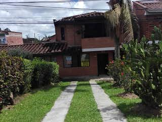 Un banco de madera sentado delante de un edificio en Casa en venta en San Antonio De Pereira 108m²
