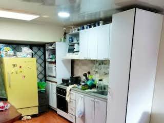 Una cocina con suelos de madera y paredes blancas en VENDO CASA  COMERCIAL EN AV. 1 DE MAYO