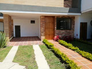 Una sala de estar con chimenea y flores en ella en Casa en venta en unidad cerrada en el municipio de La Ceja