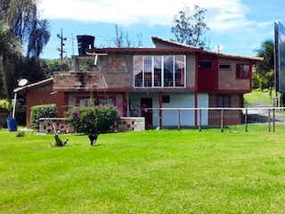 Una pequeña casa con un edificio rojo en el fondo en Venta de finca via La Ceja- Rionegro