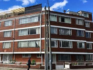 Un hombre caminando por una calle al lado de edificios altos en Apartamento En Venta En Bogota Colombia