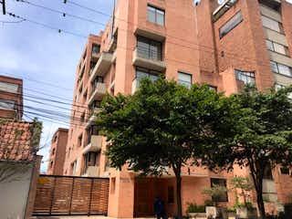 Un edificio alto con un árbol en el fondo en Apartamento En Venta En Bogota Rosales