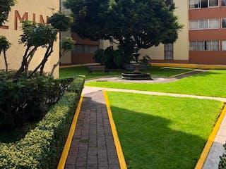 Un edificio con un banco de parque delante de él en Departamento en venta en Valle Escondido de 3 hab.