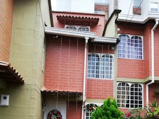 Un edificio de ladrillo con un árbol delante de él en CASA EN SABANETA