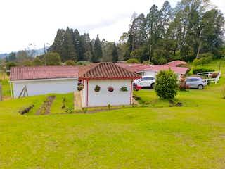 Una vista de una casa con una casa en el fondo en FINCA EN EL ALTO DE MEDINA, PIEDRAS BLANCAS /GUARNE