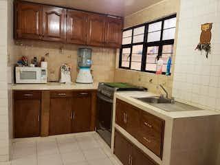 Una cocina con armarios de madera y un fregadero en Casa en venta en Lomas De Zaragoza de 6 recámaras