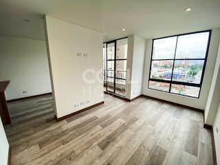Una habitación con suelos de madera y una gran ventana en Apartaestudio para estrenar en venta en Cedritos