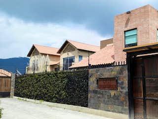 Un edificio con una torre de reloj en la parte superior en VENTA HERMOSA CASA EN CAJICA CS-004