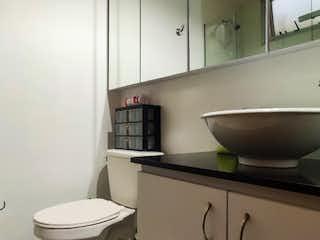 Un cuarto de baño con un inodoro y un lavabo en venta apartamento sector La Frontera