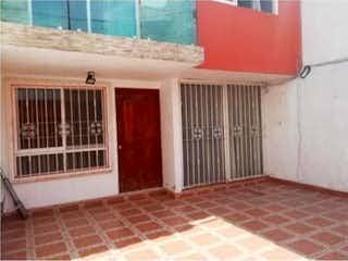 Un edificio de ladrillo rojo con un banco rojo en CASA EN  LA COL. AMPLIACION LA CONCHITA