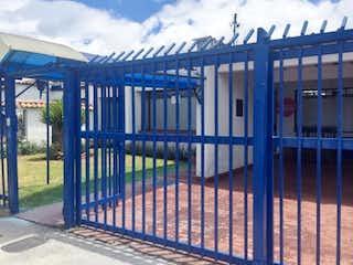 Un banco azul sentado junto a una cerca metálica en Casa