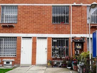 Un edificio de ladrillo con un gran edificio en el fondo en Casa En Venta En Bogota El Tintal
