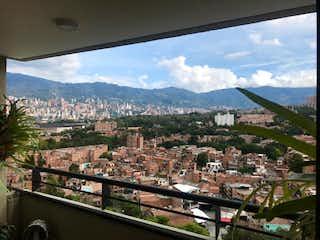 Una vista de una ciudad con montañas en el fondo en Venta de Apartamento Loma de los Bernal