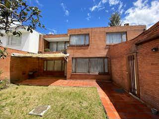Un gran edificio de ladrillo con una puerta de madera en Casa en venta en Chicó Navarra de 4 hab. con Jardín...