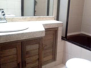 Un cuarto de baño con lavabo y un espejo en VENDEMOS APARTAMENTO EN CALLE 116