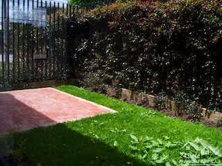 Un banco en medio de un jardín en Casa en Chía - Condominio Frutales - casas personalizadas a su gusto.