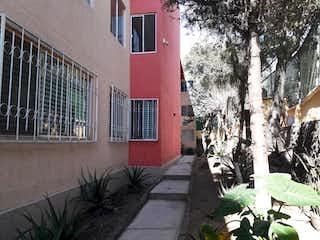 Un edificio de ladrillo rojo con un árbol en maceta en Departamento en Venta en Santa Ursula Coapa Coyoacán