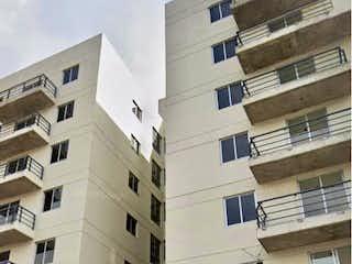 Un edificio alto con muchas ventanas en Departamento en venta en Ahuizotla de 54m²