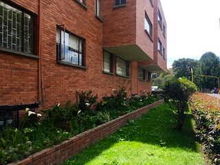 Un edificio de ladrillo con un árbol delante de él en VENDO APARTAMENTO EN CEDRITOS