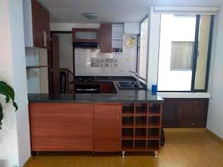 Una cocina con armarios de madera y una ventana en VENDO REMODELADO SANTA BARBARA