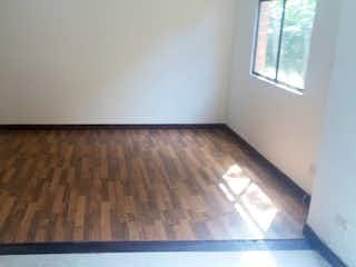 Una cama en una habitación con suelo de madera en Apartamento en venta en Zúñiga, de 83mtrs2