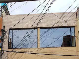Un banco de madera sentado delante de un edificio en Casa En Venta En Bogota Suba Centro
