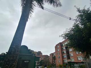 Un edificio alto con un árbol en el fondo en Apartamento en Venta LA FRONTERA