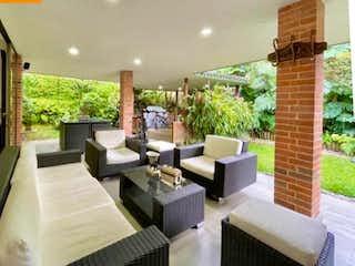 Una sala de estar llena de muebles y una gran ventana en SE VENDE HERMOSA CASA EN UNIDAD CERRADA ENVIGADO LOMA BENEDICTINOS