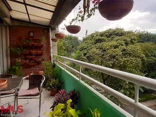 Un patio trasero con una mesa de madera y sillas en Villa De Aburra
