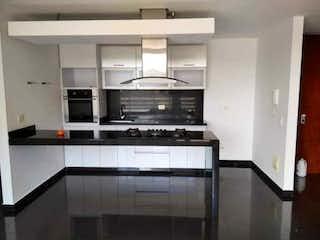 Una cocina con electrodomésticos de acero inoxidable y armarios blancos en APTO MODERNO CON VISTA AL PARQUE 109M2 - COUNTRY CALLE 135