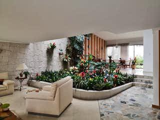 Una sala de estar llena de muebles y flores en VENTA CASA PUENTE LARGO 420M2 TERRENO