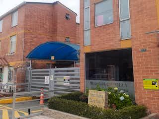 Un edificio de ladrillo rojo con un techo azul en VENTA CASA CONJUNTO RESIDENCIAL PRADOS DE CASTILLA V ETAPA