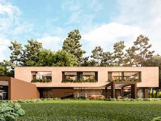 Una casa que tiene un edificio en el fondo en CASA CAMPESTRE EN VENTA EN EL ALTO DE LAS PALMAS, ENVIGADO.