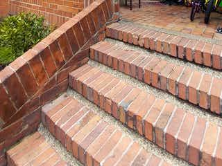 Un edificio de ladrillo con un banco en él en Casa En Venta En Bogotá Salitre
