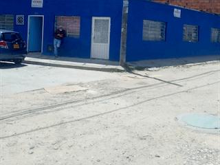 Un cartel de calle en una acera cerca de un edificio en SUPER OFERTA CASA PARA PROYECTO ALQUERIA LA FRAGUA BGTA