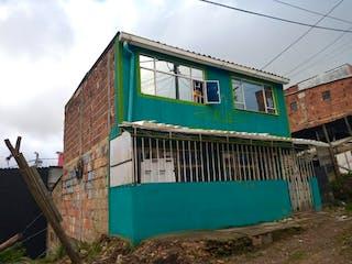 Un tren verde y blanco sentado delante de un edificio en Casa en venta en Marichuela de 3 alcoba
