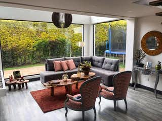 Una sala de estar llena de muebles y una gran ventana en Casa en venta en Cota, 280mt de tres niveles