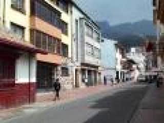 Una calle de la ciudad con gente caminando sobre ella en Casa En Venta En Bogota La Candelaria