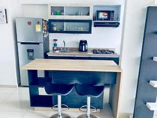 Una cocina con una mesa y un refrigerador en Apartaestudio en Venta RODEO ALTO