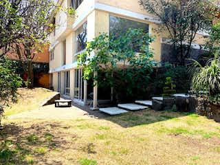 Un jardín con un banco y algunas plantas en Linda y Amplia Casa en Calle Cerrada en Venta / Fuentes del Pedregal