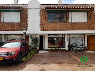 Un par de coches estacionados delante de un edificio en Casa En Venta En Bogota Cedritos-Usaquén, cuenta con 3 niveles y 2 parquederos descubiertos.