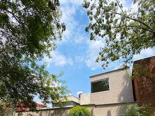 Un edificio de piedra con un árbol delante de él en Casa en VENTA en Fuentes del Pedregal