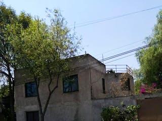 Un edificio de piedra con un árbol delante de él en CASA EN XOCHIMILCO