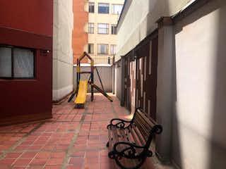 Un banco de madera sentado delante de un edificio en Apartamento En Venta En Bogota Cedritos