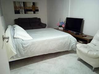 Una habitación de hotel con una cama y un televisor en VENDO APARTAMENTO ALTOS DEL POBLADO